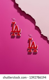 Shot of massive dangle earrings in the view of Los Angeles abbreviation, isolated asymmetrically against the pink background. The set is near pale pink ragged platform. Voguish women's fashion item.
