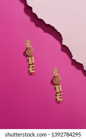 Shot of massive dangle earrings with voguish opalesce lettering. The accessory set is isolated asymmetrically on the pink background, near pale pink ragged platform. Fashionable women's accessory.
