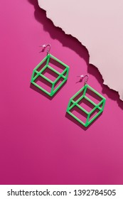 A shot of massive light green dangle earrings with 3D effect. The pin hype set is isolated asymmetrically against the pink background, near pale pink ragged platform. Stylish women's fashion item.