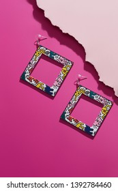Shot of massive multicolored dangle earrings in view of photo frame. The stylish set is isolated asymmetrically on the pink background, near pale pink ragged platform. Trendy women's fashion item.