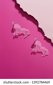 A shot of massive transparent dangle earrings in view of a horse. The voguish set is isolated asymmetrically against the pink background, near pale pink ragged platform. Trendy women's fashion item.