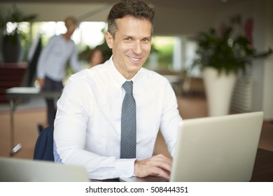 Shot of a mature businessman sitting in the office and using his laptop while working on new project. Business people working at background.