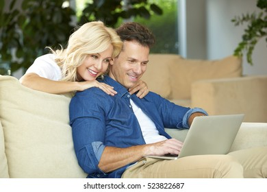 Shot of a mature couple surfing the net while relaxing on the sofa at home. Handsome middle aged man using laptop while beautiful woman bonding him and enjoying some online entertainment together.