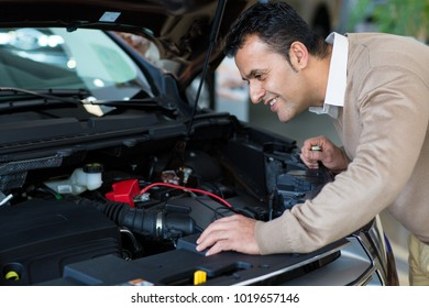 Shot of a mature male customer looking under the hood of an automobile at the dealership showroom examining engine of a car copyspace repair driving horsepower powerful vehicle transportation.