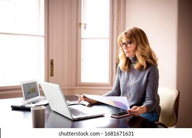 Aufnahme einer reifen Frau, die hinter ihren Laptops sitzt und von zu Hause aus arbeitet.