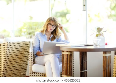 Shot of a mature woman thinking of business ideas while sitting with her laptop at the sofa at home.