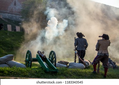 shot from a medieval cannon at festival historical reconstruction, assault fortress by soldiers with Musketeers, a lot of pyrotechnics, flashes fire, explosions and battlefield was shrouded  in smoke