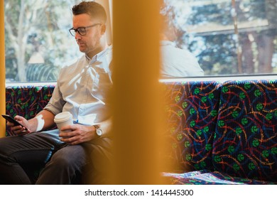 A shot of a mid-adult caucasian businessman sitting on a train commuting to work in Perth, Australia. He is using his smart phone while holding a hot drink.