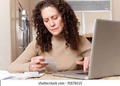 A shot of a middle age caucasian woman paying bills at home