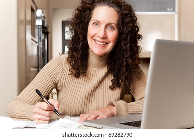 A shot of a middle age woman paying bills at home