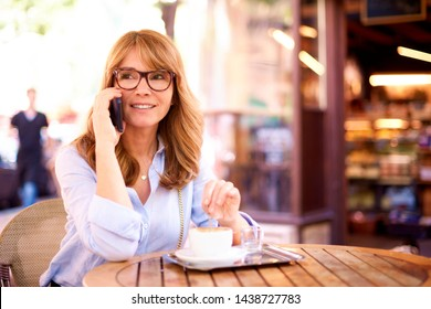 Shot of middle aged businesswoman sitting in the coffee shop and drinking espresso while talking with somebody on her mobile phone.