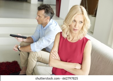 Shot of a middle aged couple in midlife crisis. Mature husband sitting on sofa and using remote control while beautiful woman standing behind the man and they having domestic dispute.