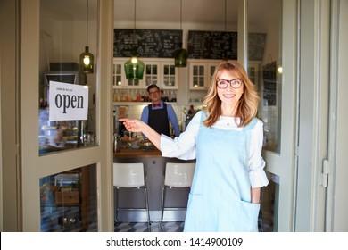 Aufnahmen von mittelalterlicher Eigentümerin, die Schürze trägt und Ihnen lächelt, während sie auf ihren Gast in ihrem Kaffeehaus wartet. Familienbetrieb.