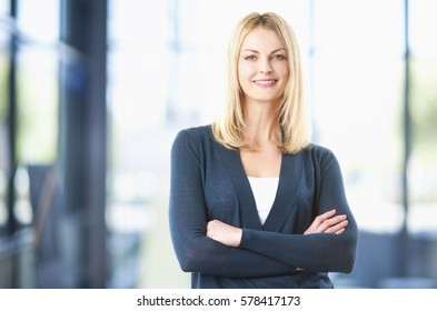 Shot of a middle businesswoman standing in her office while looking at camera and smiling.