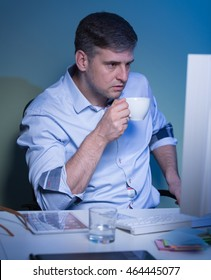Shot of a middle-aged businessman staying late in his office and drinking coffee