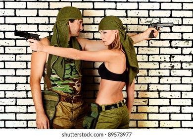 Shot of a military couple posing against brick wall.