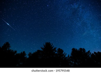 A shot of the milky way and an Iridium flare in the night sky in the Blue Ridge Mountains of North Carolina