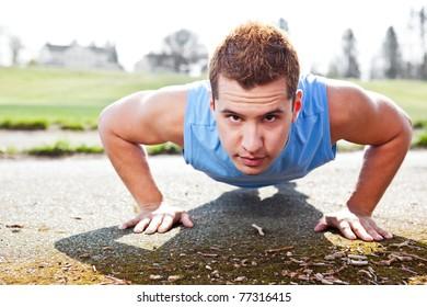 A shot of a mixed race man doing push up outdoor