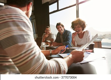 Shot of mixed race young people sitting at a table discussing new and creative business ideas. Smiling african woman sitting with colleagues in a meeting.