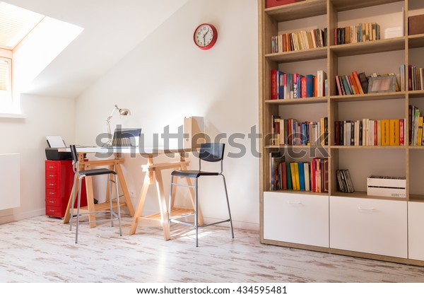 Shot of a modern study with a desk and a bookshelf