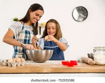 Shot of a mother and daughter having fun in the kitchen and learning to make a cake