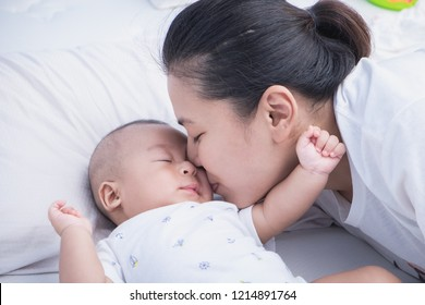 Shot of Mother kissing her adorable Asian newborn baby boy in the bedroom at home. Child in beautiful mom embrace cuddling with tenderness. Breastfeeding or early childhood development concept