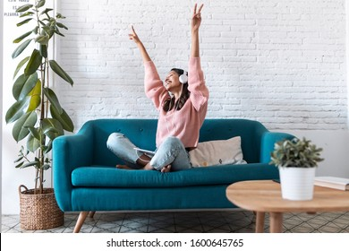 Shot of motivated young woman listening to music with digital tablet while sitting on sofa at home.
