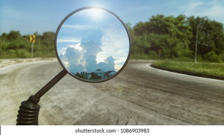 Shot of motorcycle rare view mirror reflecting beautiful sunlight behind white fluffy cloud and road ahead as background.