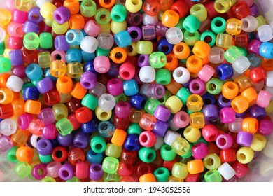 A shot of multi-colored plastic beads for handicrafts scattered on the table