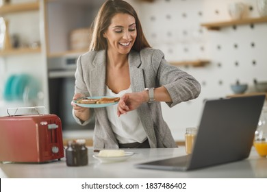 Shot of a multi-tasking young business woman having a breakfast and using laptop in her kitchen while getting ready to go to work.
