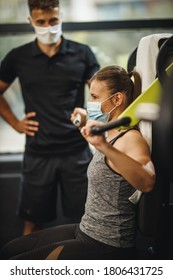 Shot of a muscular young woman with protective mask working out with personal trainer at the gym machine during Covid-19 pandemic. She is pumping up her shoulder muscule with heavy weight.