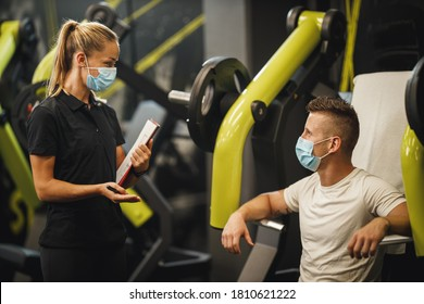 Shot of a muscular young woman with protective mask working out with personal trainer at the gym machine during Covid-19 pandemic. She is pumping up her chest muscule with heavy weight.