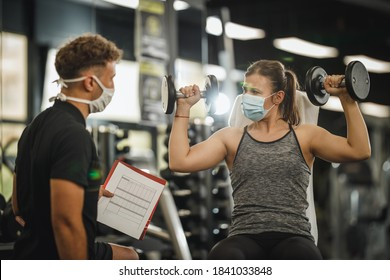 Shot of a muscular young woman with protective mask working out with personal trainer at the gym during Covid-19 pandemic. She is pumping up her muscule with dumbbell.