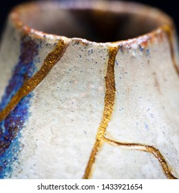 A shot of the neck of a vase I repaired with gold powder and urushi lacquer with the Japanese art form of kintsugi in a square aspect ratio.