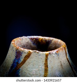 A shot of the neck of a vase I repaired with gold powder and urushi lacquer with the Japanese art form of kintsugi in a square aspect ratio with room for text at the top.