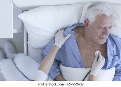 Shot of a nurse doing a medical examination using the stethoscope of senior patient lying on a hospital bed
