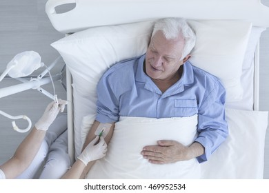 Shot of a nurse drawing blood of senior patient lying on a hospital bed
