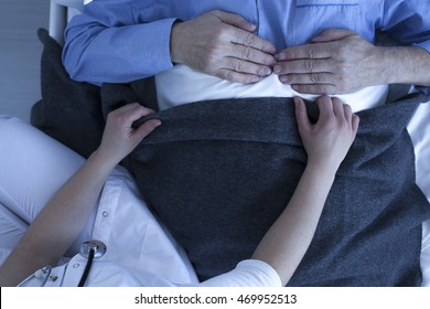 Shot of nurse's arms correcting the older patient's bedding