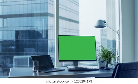 Shot of the Office Desk with Green Mock-up Screen Personal Computer Standing on it. Modern Stylish Room with a Big City Business District View.
