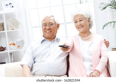 A shot of old couple watching TV at home