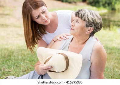 Shot of an old lady sitting on the grass on a sunny day, feeling faint, and a young woman assisting her