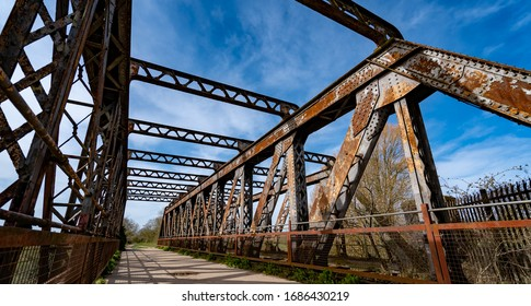 Shot of old rusty bridge set against a countryside and blue sky background