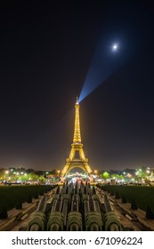 Shot on April 12, 2017: Eiffel Tower sharp light on the moon in clear night sky, Paris, France.