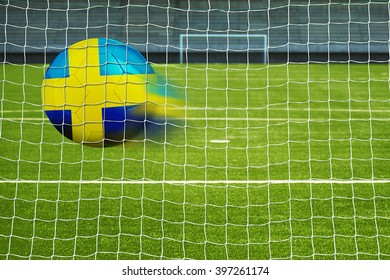 Shot on goal, soccer ball with the flag of Sweden in the net