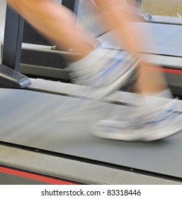 Shot on location an older male running on treadmill with very slow shutter speed.  The treadmill is clear and focus on,  athletes legs motion blurred.