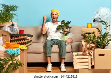 Shot of overjoyed guy clenches fist, poses at sofa, holds wrapped houseplant, moves in new modern house, being estate owner, has to unpack personal stuff from boxes. Home, tenant, relocation concept
