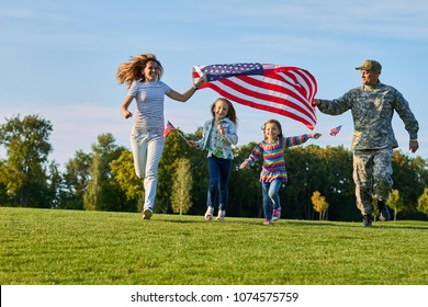 Shot of patriotic family running with flag. US soldier and his happy family.