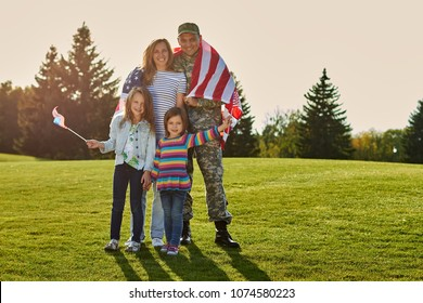 Shot of patriotic family. Soldier with his wife and daughters with american flags.