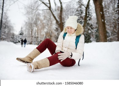Shot of person during falling in snowy winter park. Woman slip on the icy path, fell, injury knee and sitting in the snow. Danger of season trauma.