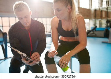 Shot of a personal trainer helping a gym member with her exercise plan. Trainer goes through fitness plan with client in the health club.